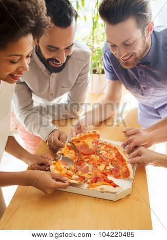 business, food, lunch and people concept - happy business team eating pizza in office