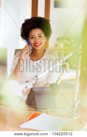 business, startup and people concept - happy african american businesswoman or creative worker calling on smartphone at office