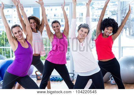 Portrait of happy women exercising with arms raised in fitness studio