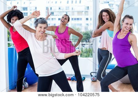 Cheerful women exercising with arms raised in fitness studio