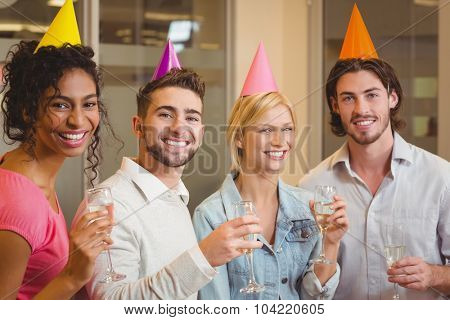 Portrait of smiling colleagues holding champagne flute in birthday party at creative office