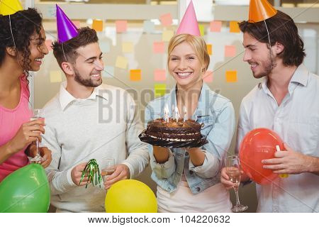 Portrait of happy businesswoman holding birthday cake while colleagues looking at her in creative office
