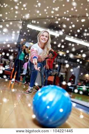 people, leisure, sport and entertainment concept - happy young woman throwing ball in bowling club at winter season