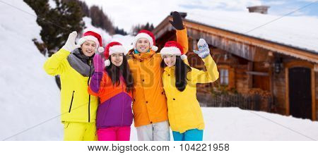 winter holidays, christmas, friendship and people concept - happy friends in santa hats and ski suits waving hands outdoors over wooden country house background and snow