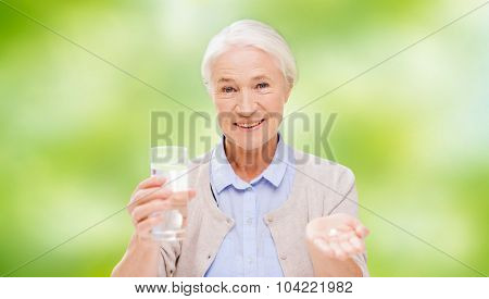 age, medicine, health care and people concept - happy senior woman with pills and glass of water over green natural background