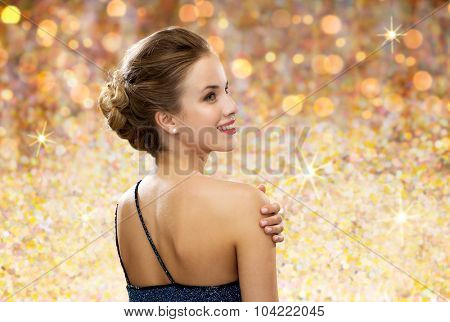 people, holidays and glamour concept - smiling woman in evening dress from back over golden lights background