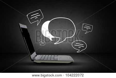 technology and communication concept - open laptop computer with blank screen and text bubbles over dark gray background