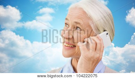technology, communication age and people concept - happy senior woman with smartphone calling over blue sky and clouds background