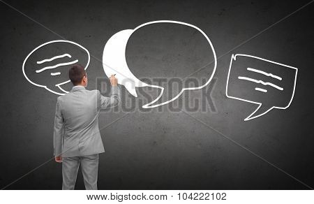 business, people, communication and information concept - businessman drawing text bubbles from back over dark gray concrete wall background