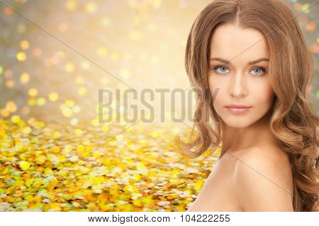 people, beauty, holidays , hair and skin care concept - beautiful woman with curly hairstyle over yellow autumn lights background
