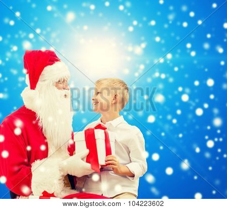 holidays, christmas, childhood and people concept - smiling little boy with santa claus and gifts over blue snowy background