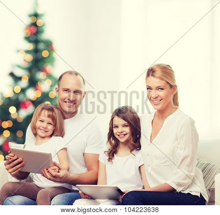 family, holidays, technology and people - smiling mother, father and little girls with tablet pc computers over living room and christmas tree background