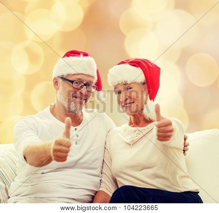 family, holidays, christmas, age and people concept - happy senior couple in santa helper hats sitting on sofa over beige lights background and showing thumbs up gesture