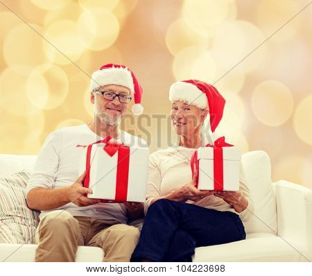 family, holidays, christmas, age and people concept - happy senior couple in santa helper hats with gift boxes over beige background