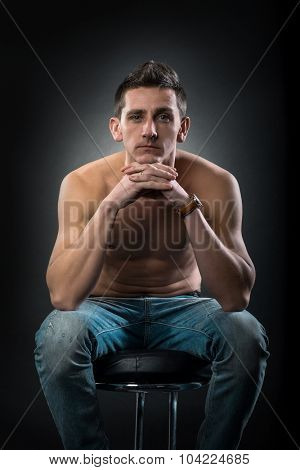 Contemporary man in jeans sitting