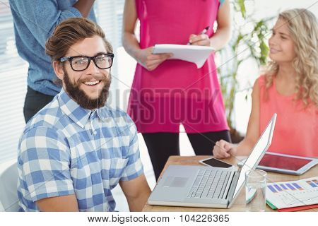 Portrait of smiling man with coworkers discussing at desk