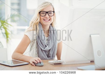 Portrait of smiling woman using computer while sitting at desk