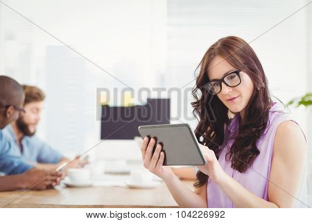 Thoughtful woman holding digital tablet at desk in office