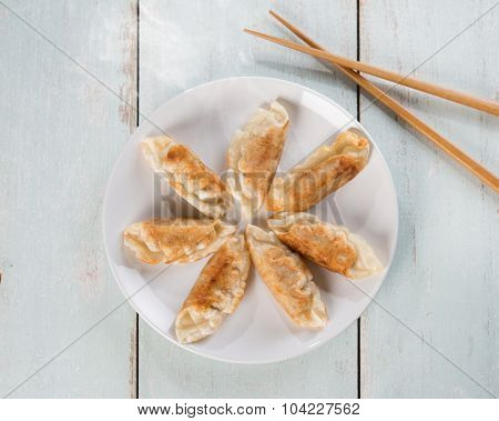 Top view fresh pan fried dumplings on plate with hot steams. Asian dish on rustic vintage wooden background.