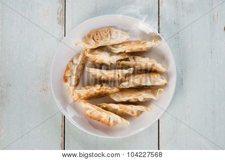 Top view fresh pan fried dumplings on plate with hot steams. Asian appetizer on rustic vintage wooden background.