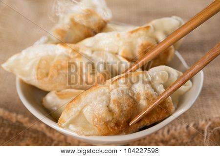 Close up fresh pan fried dumplings on bowl with chopsticks and hot steams. Asian food on rustic vintage wooden background.