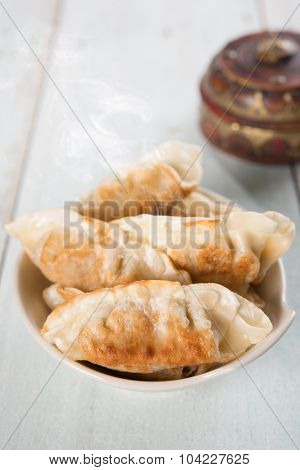 Fresh pan fried dumplings on plate with hot steams. Asian food on rustic vintage wooden background.