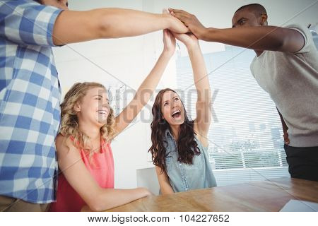 Smiling business people giving high five at desk in office