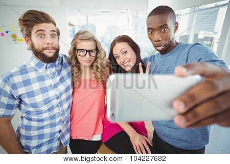 Business people making face while taking selfie at office