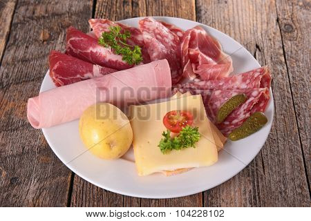 plate with raclette cheese and delicatessen