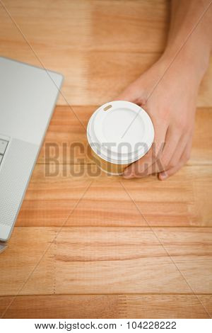 Cropped of man holding disposable cup on table in office