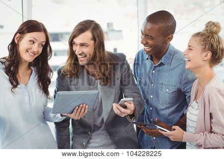 Happy business team using technology while standing at office