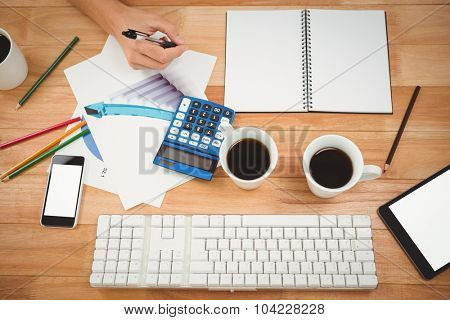 Overhead view of black coffee and technologies with documents on table in office