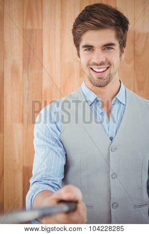 Portrait of happy businessman holding selfie stick against wooden wall