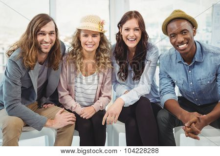 Portrait of smiling business people sitting on chair in office