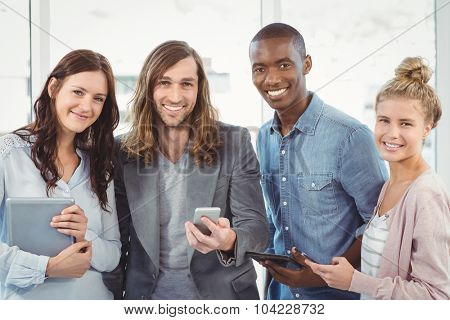 Portrait of smiling business team using technology while standing at office