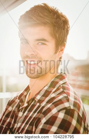 Close-up portrait of happy hipster standing by window at office