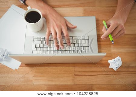 Cropped image of man with coffee and pen working on laptop at desk in office