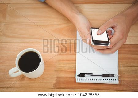 Cropped image of hipster using smartphone with coffee and notepad on table in office