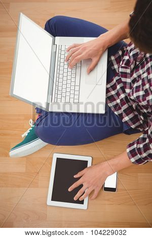 Cropped image of hipster sitting with laptop on top using digital tablet in office