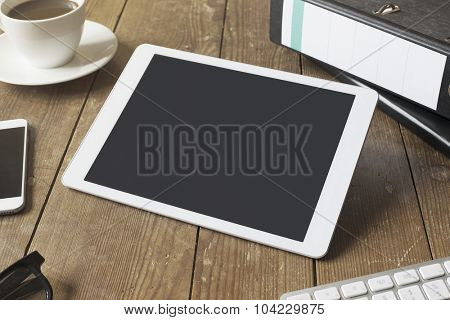 empty tablet computer on a wooden workspace