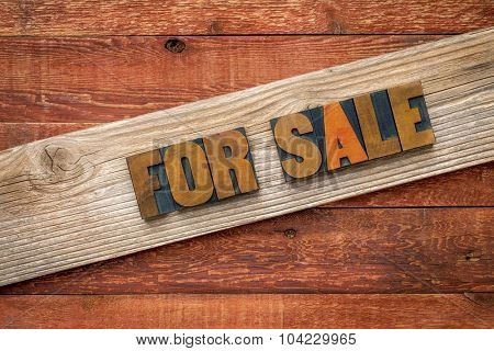For sale sign - text in letterpress wood type over a grained cedar plank against rustic barn wood