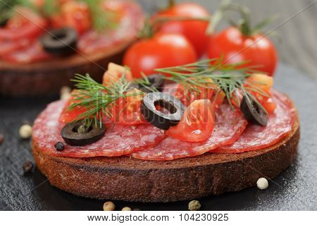 rye sandwich with salami and tomatoes on wood table