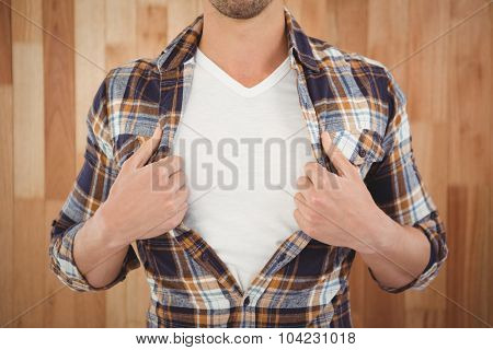 Mid section of hipster opening shirt in superhero style against wooden wall