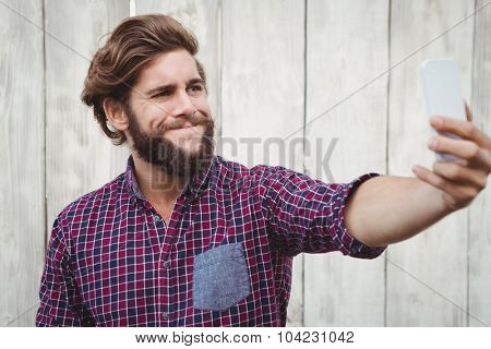 Hipster making face while taking selfie against wooden fence