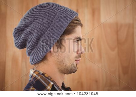 Profile view of confident hipster against wooden wall in office