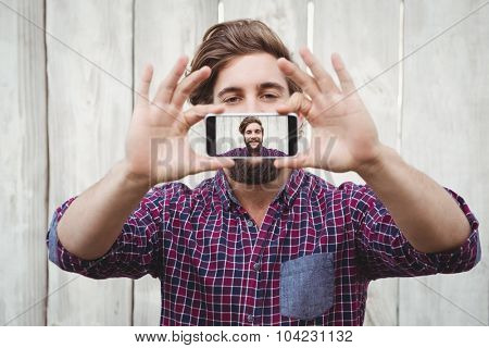 Hipster taking self portrait on smartphone against wooden fence