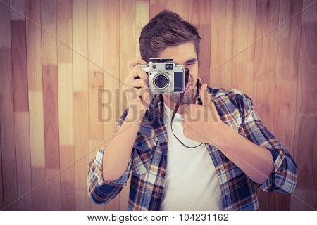 Hipster showing thumbs up while photographing against wooden wall