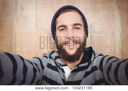 Portrait of happy hipster with hooded shirt against wooden wall