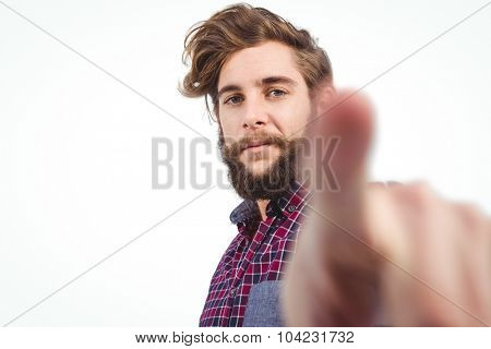 Portrait of confident hipster pointing against white background