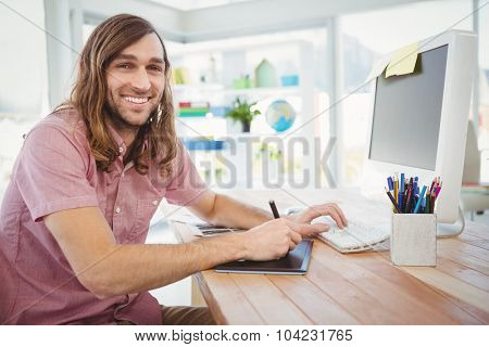 Portrait of happy hipster working on graphics tablet and computer at desk in office